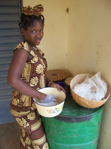 Fulani girl mixing millet and milk to make chobbal porridge