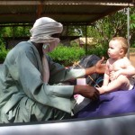 fulani man reaches out to white baby